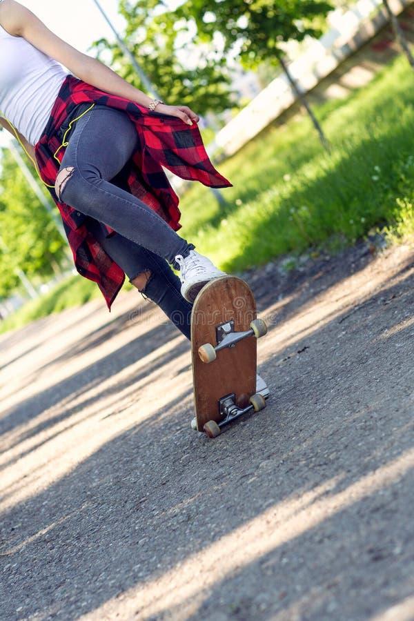 Skater da menina - p?s desportivos que skateboarding no parque imagem de stock