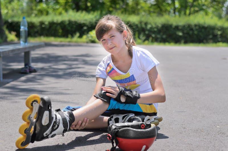 Skater do rolo que olha seu braço ferido foto de stock