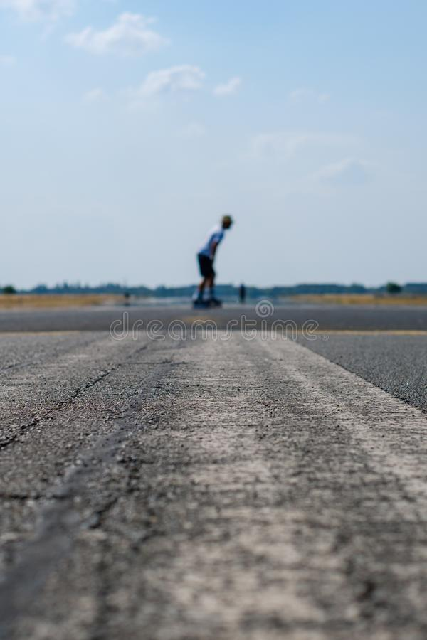 Skater on empty asphalt road / runway on former airport royalty free stock photo
