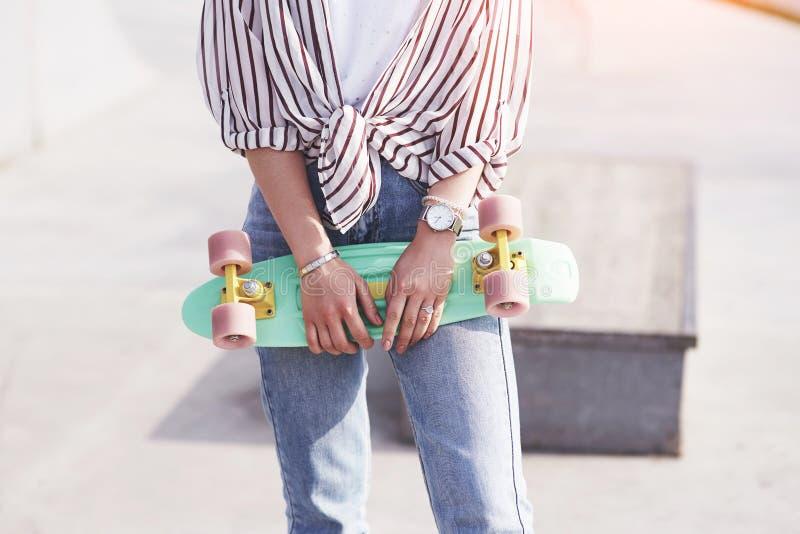 Skater fêmea adolescente bonito que senta-se na rampa no parque do patim Conceito de atividades urbanas do verão imagens de stock