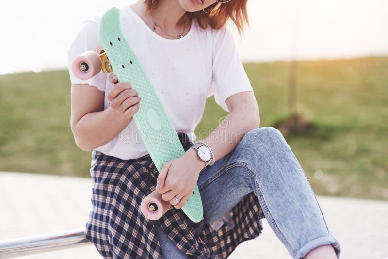 Skater fêmea adolescente bonito que senta-se na rampa no parque do patim Conceito de atividades urbanas do verão imagem de stock royalty free