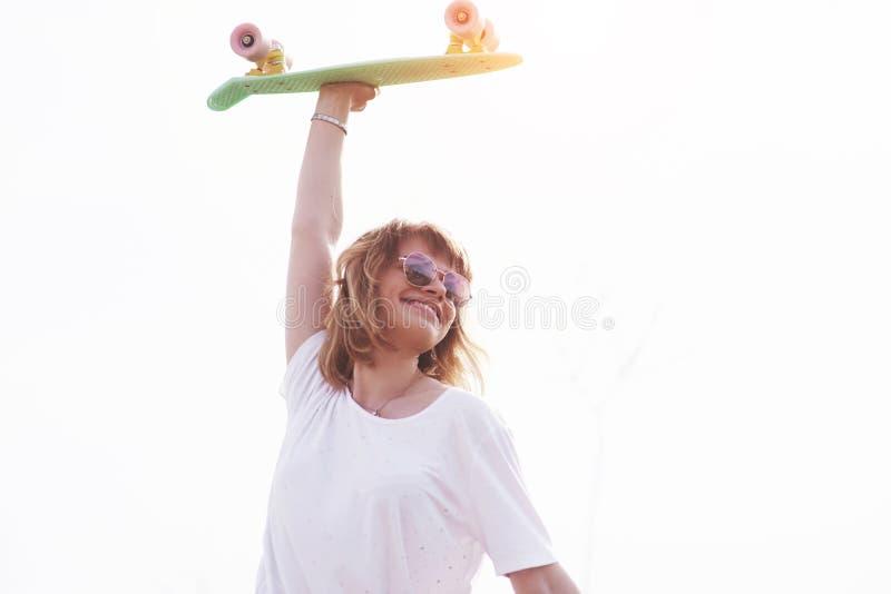 Skater fêmea adolescente bonito que senta-se na rampa no parque do patim Conceito de atividades urbanas do verão foto de stock royalty free