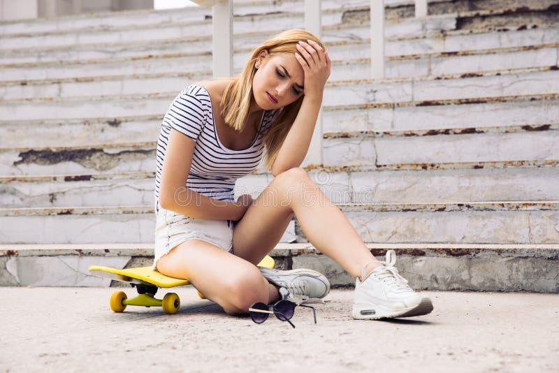Skater fêmea novo que tem a dor de cabeça imagens de stock