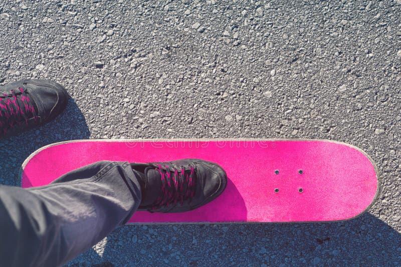 Skater feet on pink skateboard royalty free stock photography