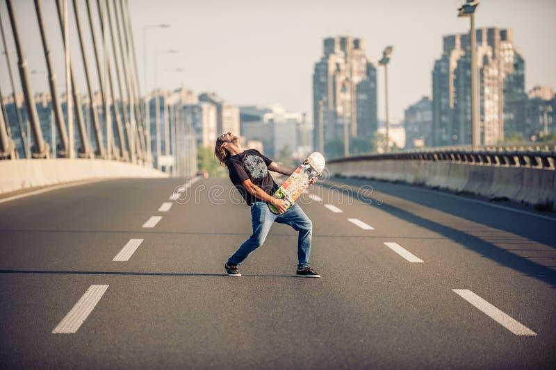 Skater feliz en el puente que toca la guitarra en su boa del patín imágenes de archivo libres de regalías