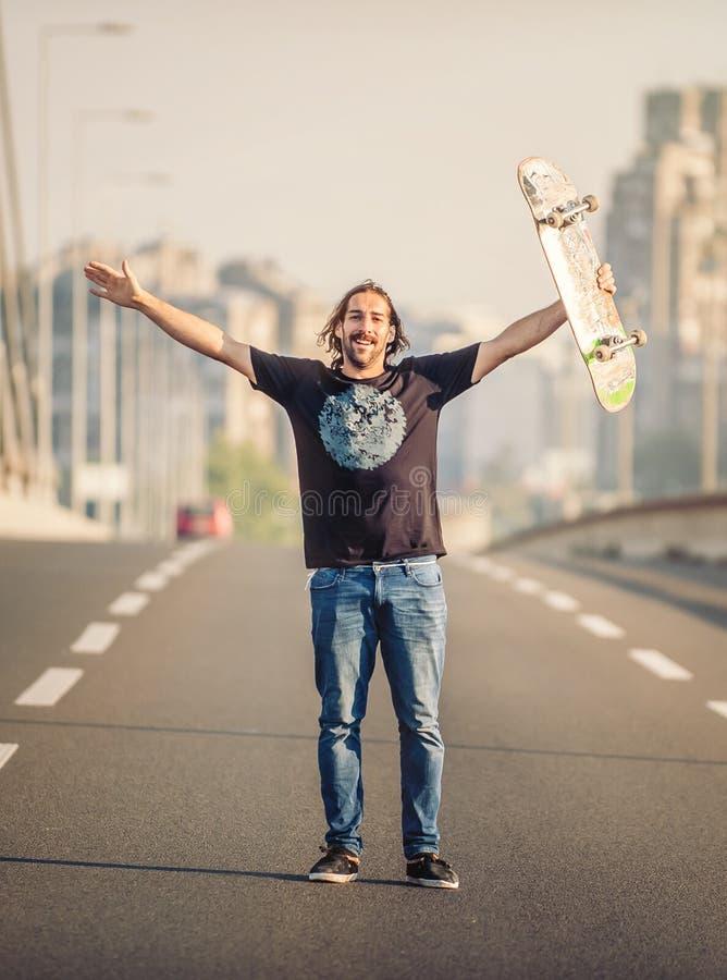 Skater feliz que se coloca en el puente del camino y que aumenta su h fotografía de archivo