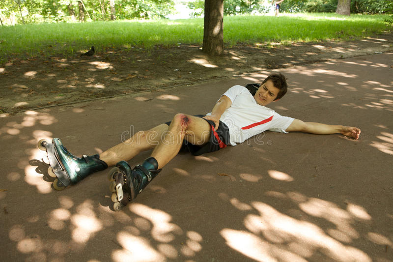 Skater injured and clutching leg stock photo
