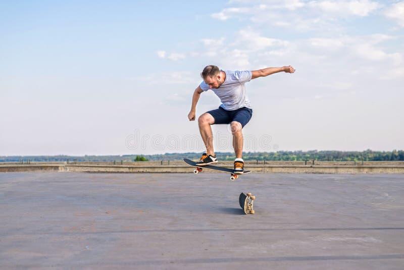 Skater joven que realiza un truco del tirón en un salto en el camino, el espacio libre foto de archivo