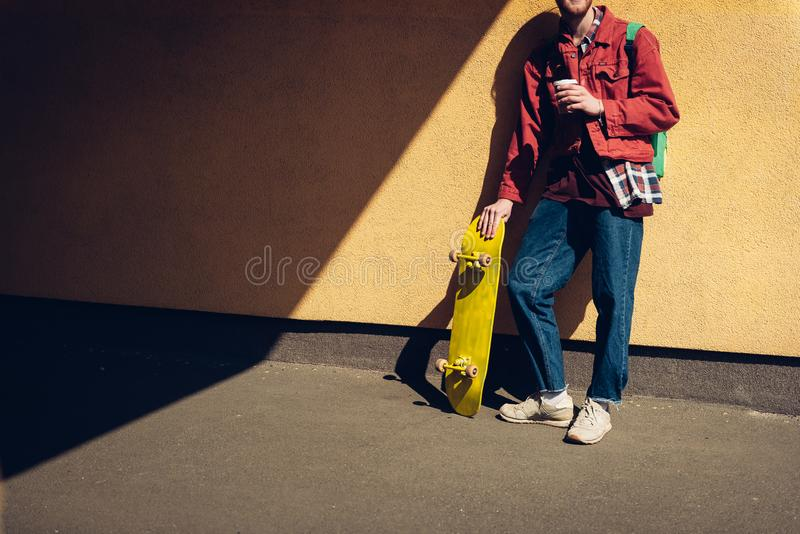 Skater man with coffee leaning on wall. Urban lifestyle and activity. Full length cropped head portrait of hipster guy leaning on building wall with yellow royalty free stock photo