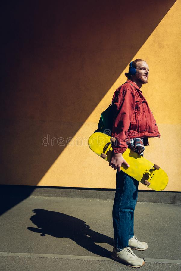 Skater man listen to music via headphones. Urban lifestyle and activity. Full length side on portrait of young smiling hipster guy with yellow skateboard stock images