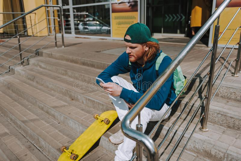 Skater man with mobile phone on store stairs. Urban lifestyle and activity. Full length portrait of young hipster guy sitting on stairs of store with skateboard stock photos
