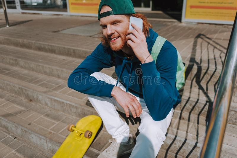 Skater man talking by mobile phone on stairs. Urban lifestyle and activity. Full length close up portrait of young hipster guy sitting on stairs of store with stock photo