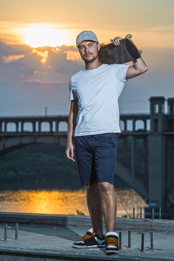 Skater masculino novo em um fundo do por do sol colorido, espaço livre fotos de stock