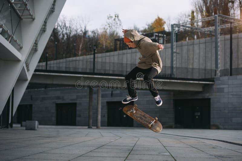 skater no equipamento do streetwear que executa o truque do salto fotografia de stock