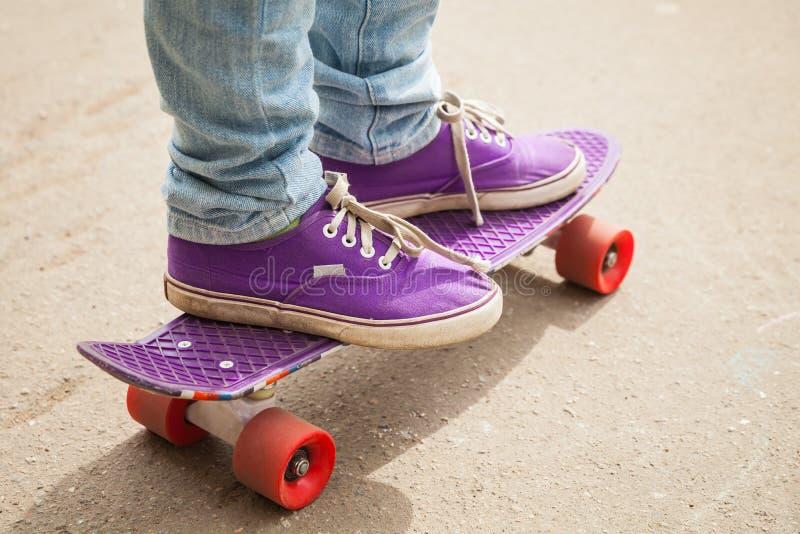 Skater novo nos gumshoes que estão em seu patim fotografia de stock royalty free