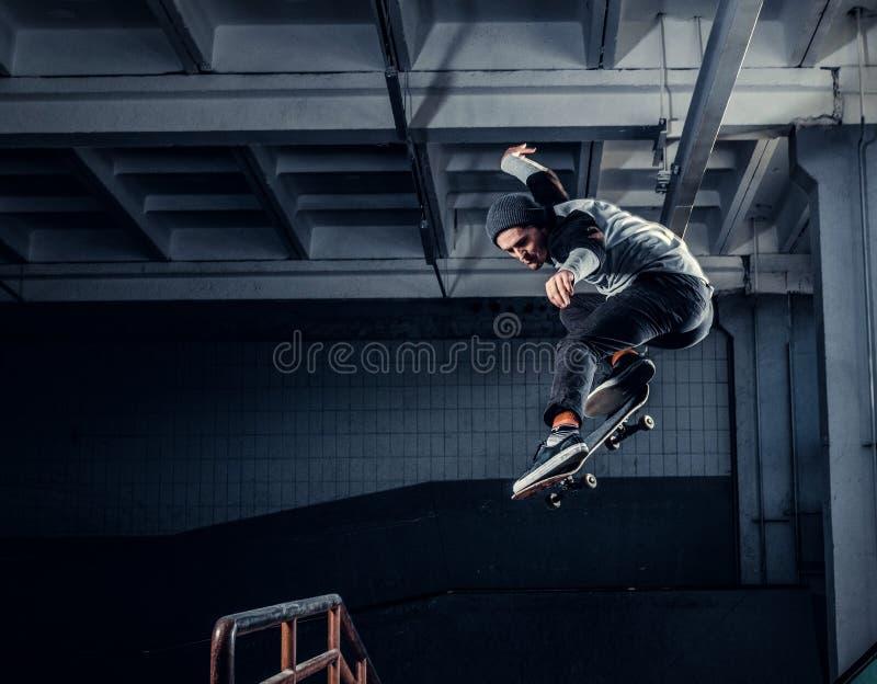 Skater novo que executa um truque na mini rampa no parque do patim interno foto de stock royalty free