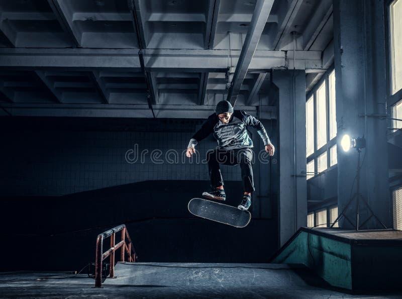 Skater novo que executa um truque na mini rampa no parque do patim interno imagem de stock