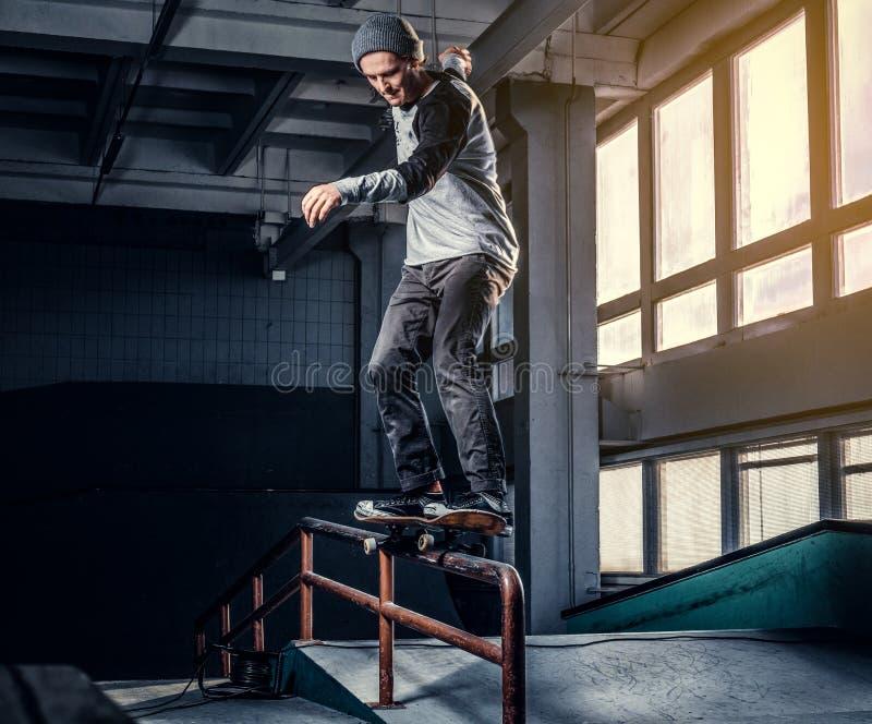 Skater novo que executa um truque na mini rampa no parque do patim interno imagem de stock royalty free