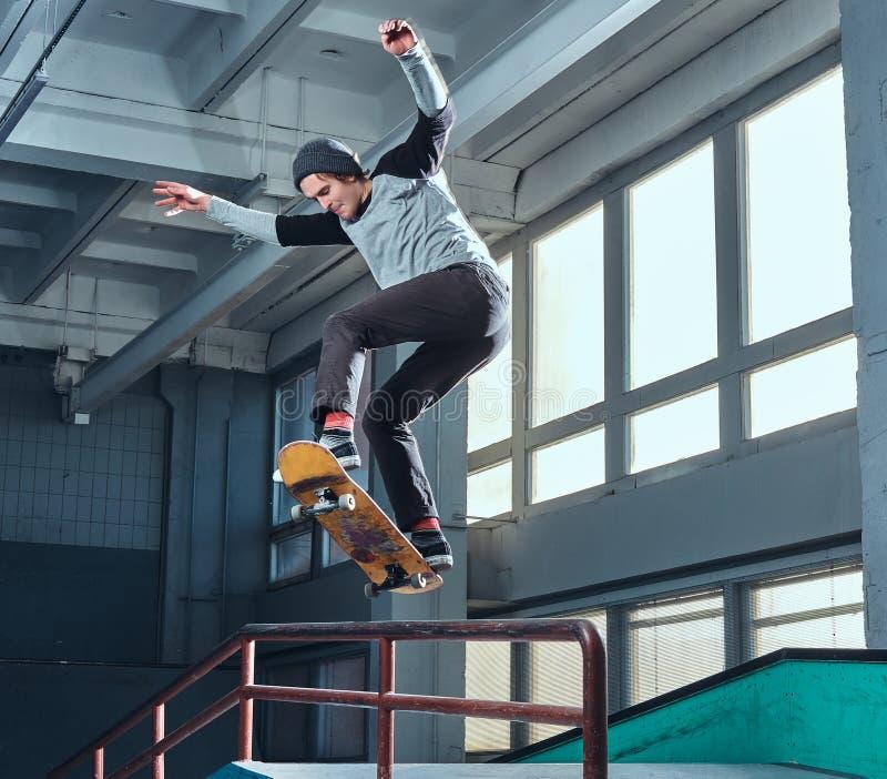 Skater novo que executa um truque na mini rampa no parque do patim interno foto de stock