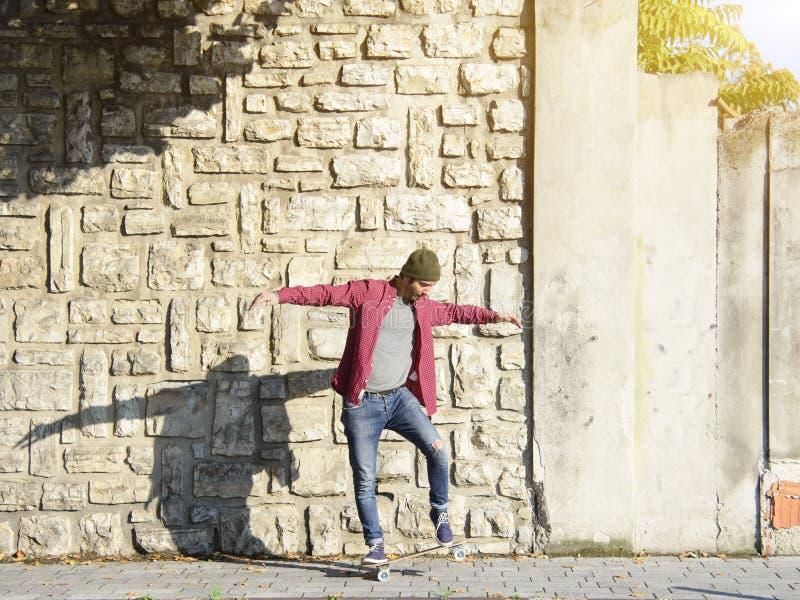 Skater que dá certo em seu patim na cidade imagem de stock