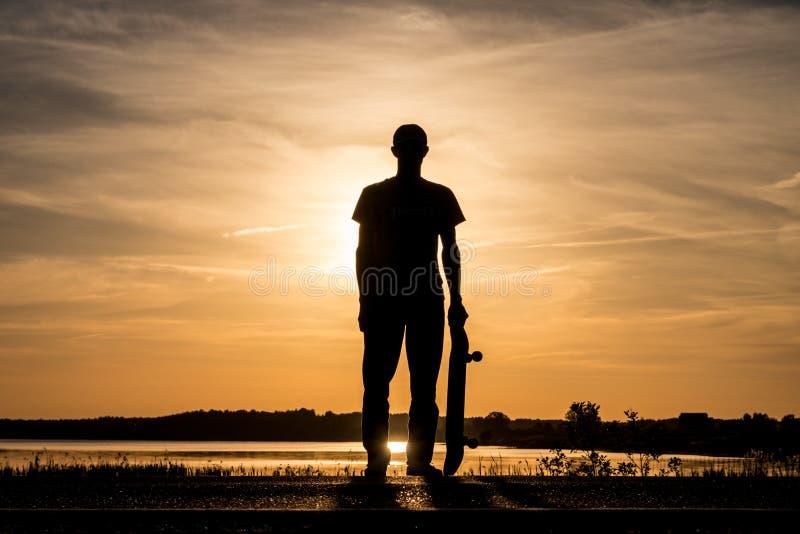 Skater que está na estrada contra o por do sol e que guarda um skate em uma mão foto de stock