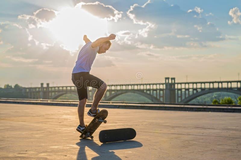 Skater que faz um truque em um salto no por do sol imagem de stock