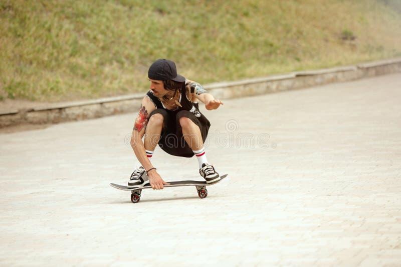 Skater que faz um truque na rua da cidade cloudly no dia imagem de stock