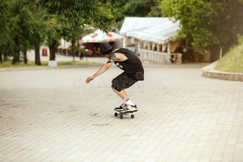 Skater que faz um truque na rua da cidade cloudly no dia fotos de stock royalty free