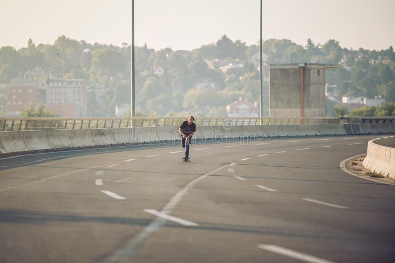 Skater que monta um patim sobre uma ponte da estrada de cidade Borla s imagem de stock
