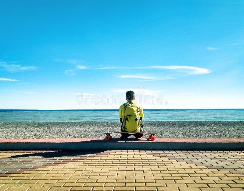 Skater que senta-se e que relaxa no longboard fotos de stock royalty free