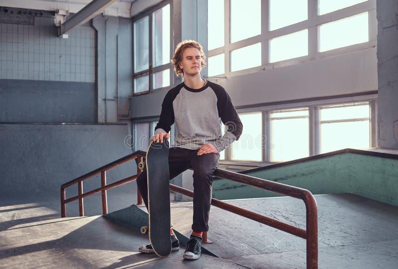Skater ruivo novo que guarda sua placa ao sentar-se em um trilho da moagem no skatepark dentro imagem de stock royalty free