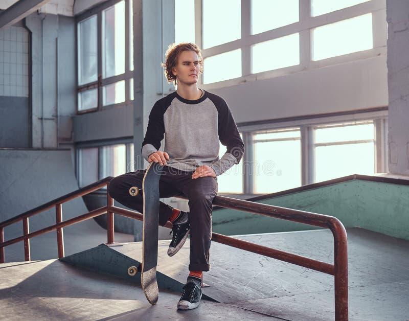 Skater ruivo novo que guarda sua placa ao sentar-se em um trilho da moagem no skatepark dentro foto de stock