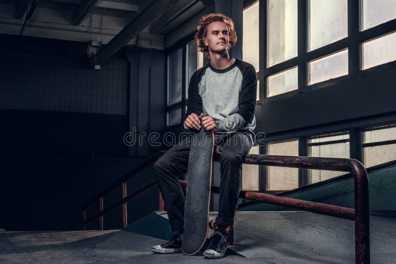 Skater ruivo novo que guarda sua placa ao sentar-se em um trilho da moagem no skatepark dentro fotos de stock