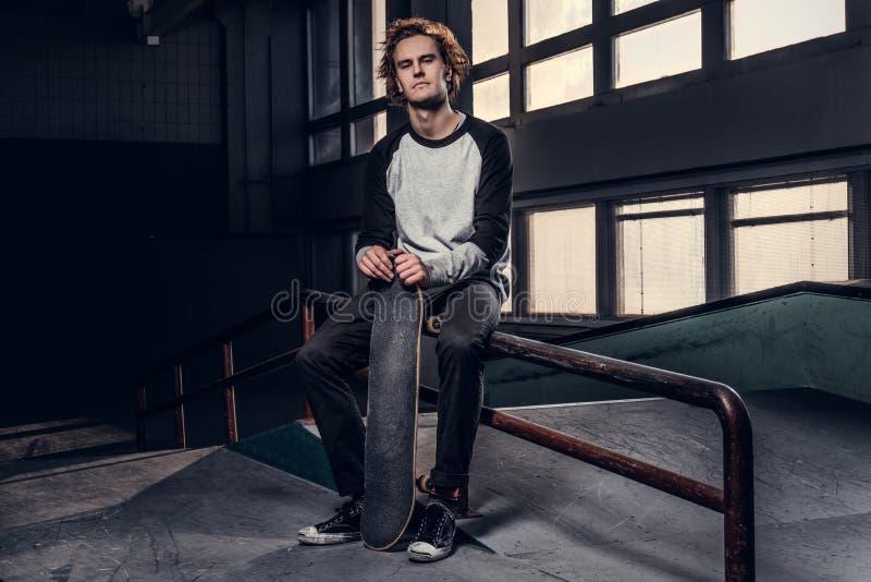 Skater ruivo novo que guarda sua placa ao sentar-se em um trilho da moagem no skatepark dentro foto de stock royalty free