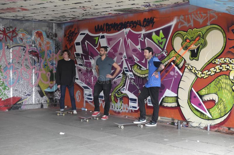Skateboarders  waiting their turn, the Undercroft,London,UK. Three young board skaters standing against a wall covered with graffiti stock image