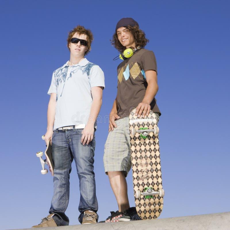 Skateres adolescentes sobre a rampa imagens de stock