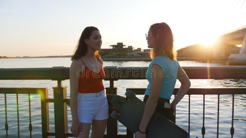 Skateres de las mujeres jovenes que se colocan en el muelle y que hablan - puesta del sol imagen de archivo