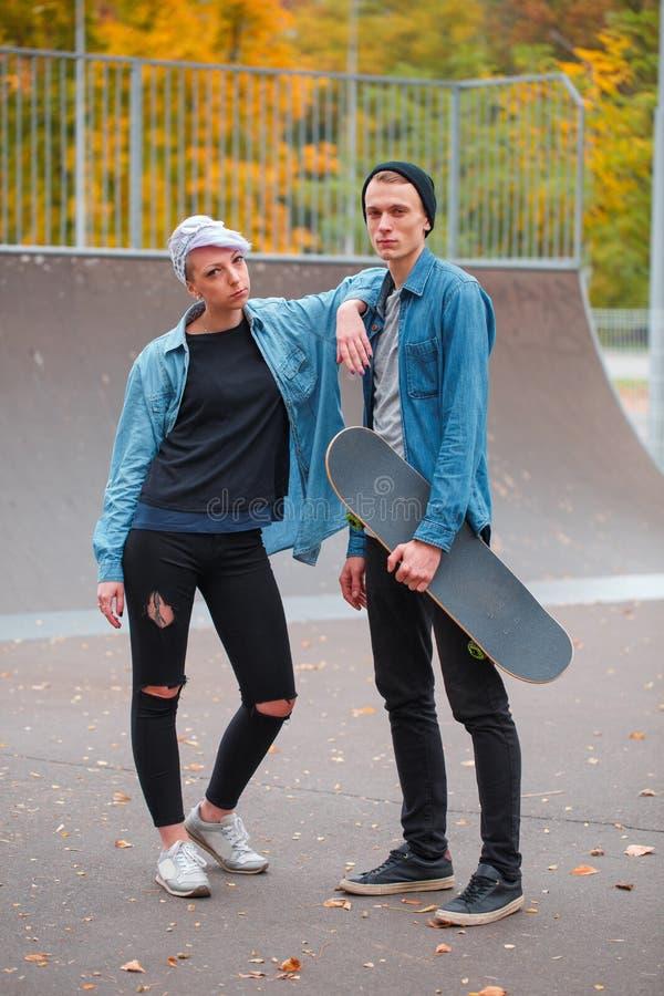 Skateres jovenes del individuo y de la muchacha, al aire libre en un día brillante del otoño foto de archivo