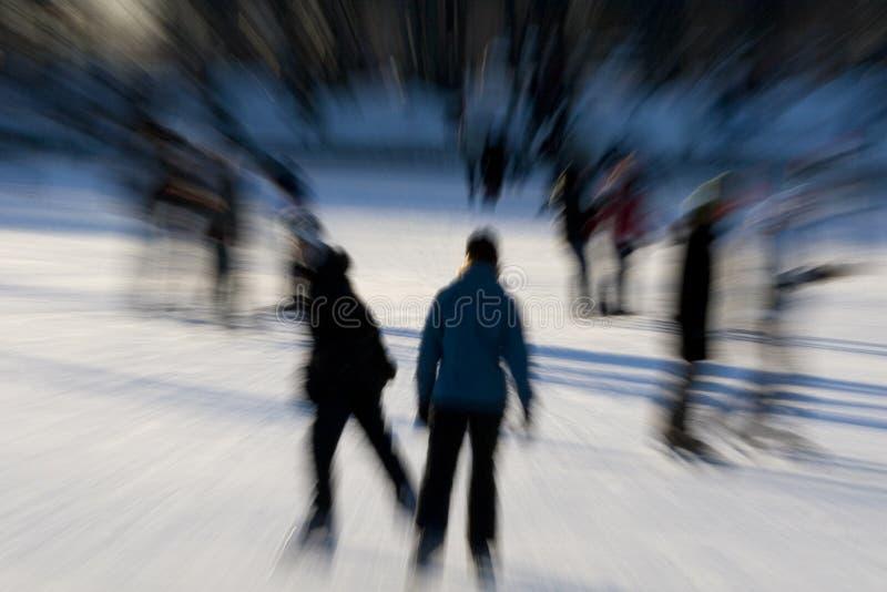 Skaters skating on pond royalty free stock photo