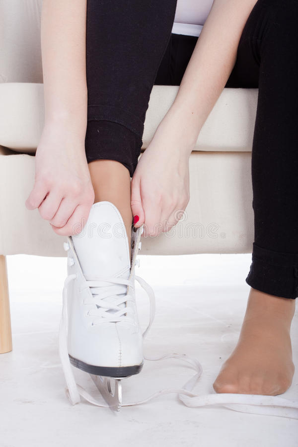 Skates. The image of a leg of a girl, puts skates on her feet stock photography