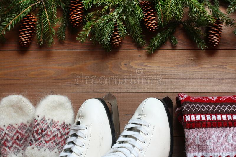 The skates, sweater and mittens on a wooden background stock photo