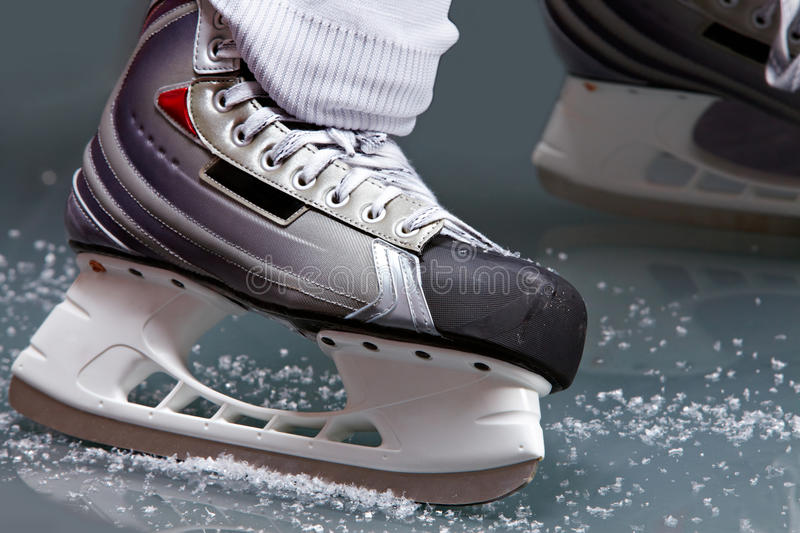 Skating. Close-up of skates on player feet during ice hockey royalty free stock photography