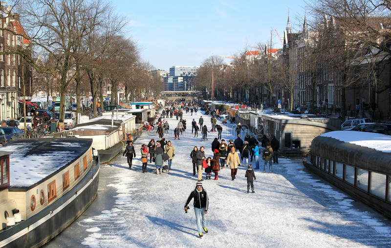 Skating over the dutch frozen canals in Amsterdam. The Amsterdam canals are not frozen very often, but now people can walk, skate and and take their buggies upon royalty free stock photo