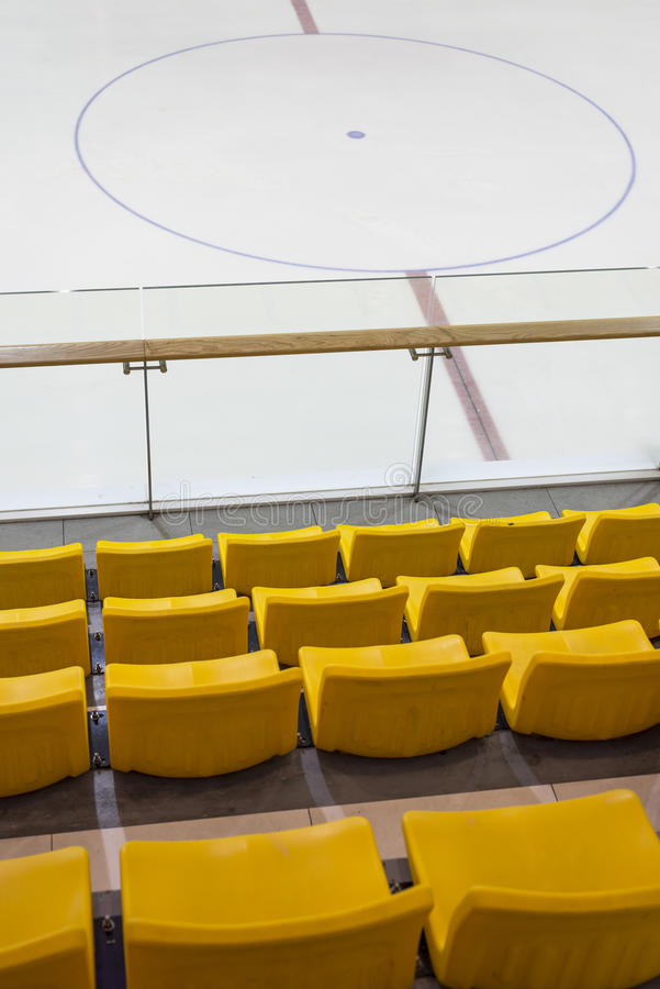 Skating Rink. Indoor ice skating and hockey rink with yellow chair and glass railing royalty free stock photo