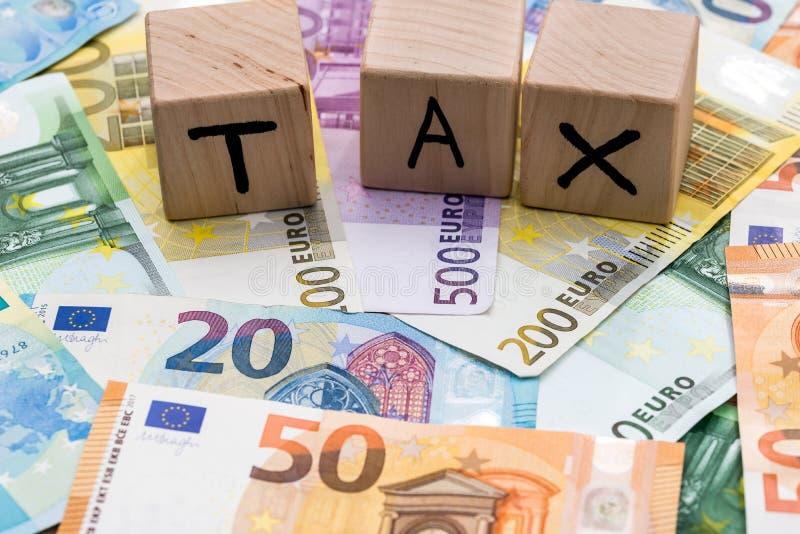Skatt på träkuber på euroräkningar som bakgrund arkivfoto