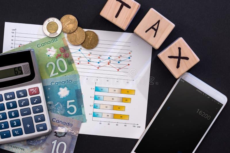 Skattbegrepp med den kanadensiska dollaren, affärsgrafen och telefonen fotografering för bildbyråer