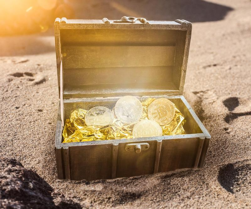 Skattbröstkorgen som fylldes med bitcoins som omgavs av guld- glöd burried delvist, i sand arkivbild