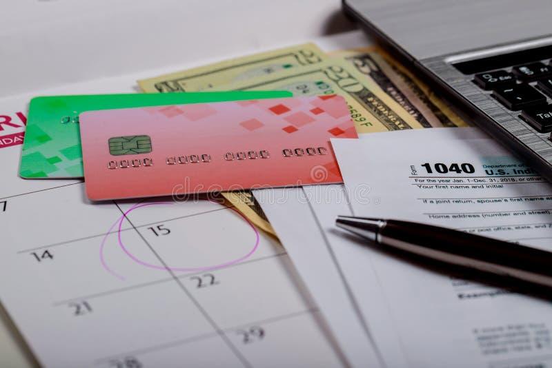 Skattform, pengar och kalender för 1040 USA med U S-dollar pengar och dator royaltyfri fotografi