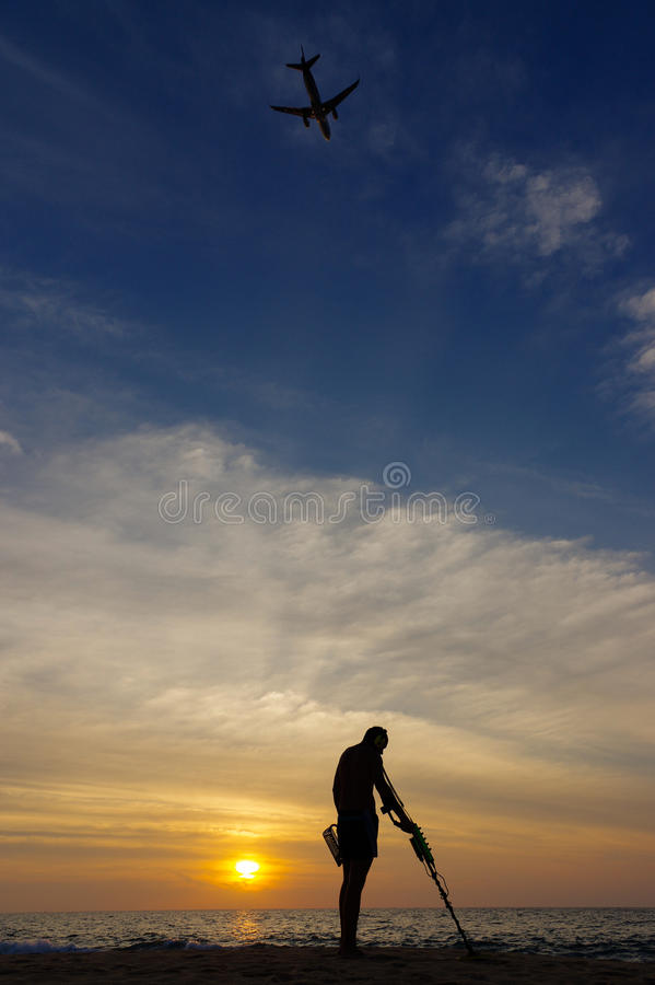 Skattjägare med metalldetektorn på solnedgång stranden ett plan i himlen arkivbild