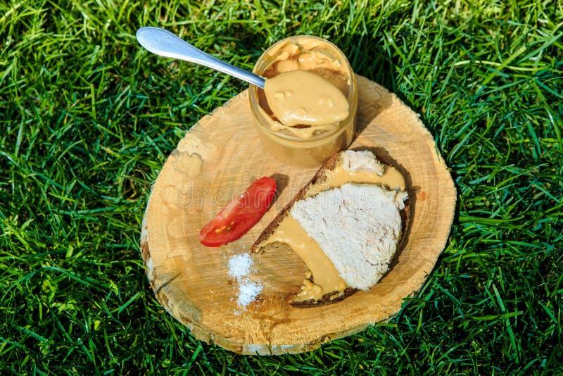 Sked av jordnötsmör på träplattan med köttsmörgåsen arkivbilder
